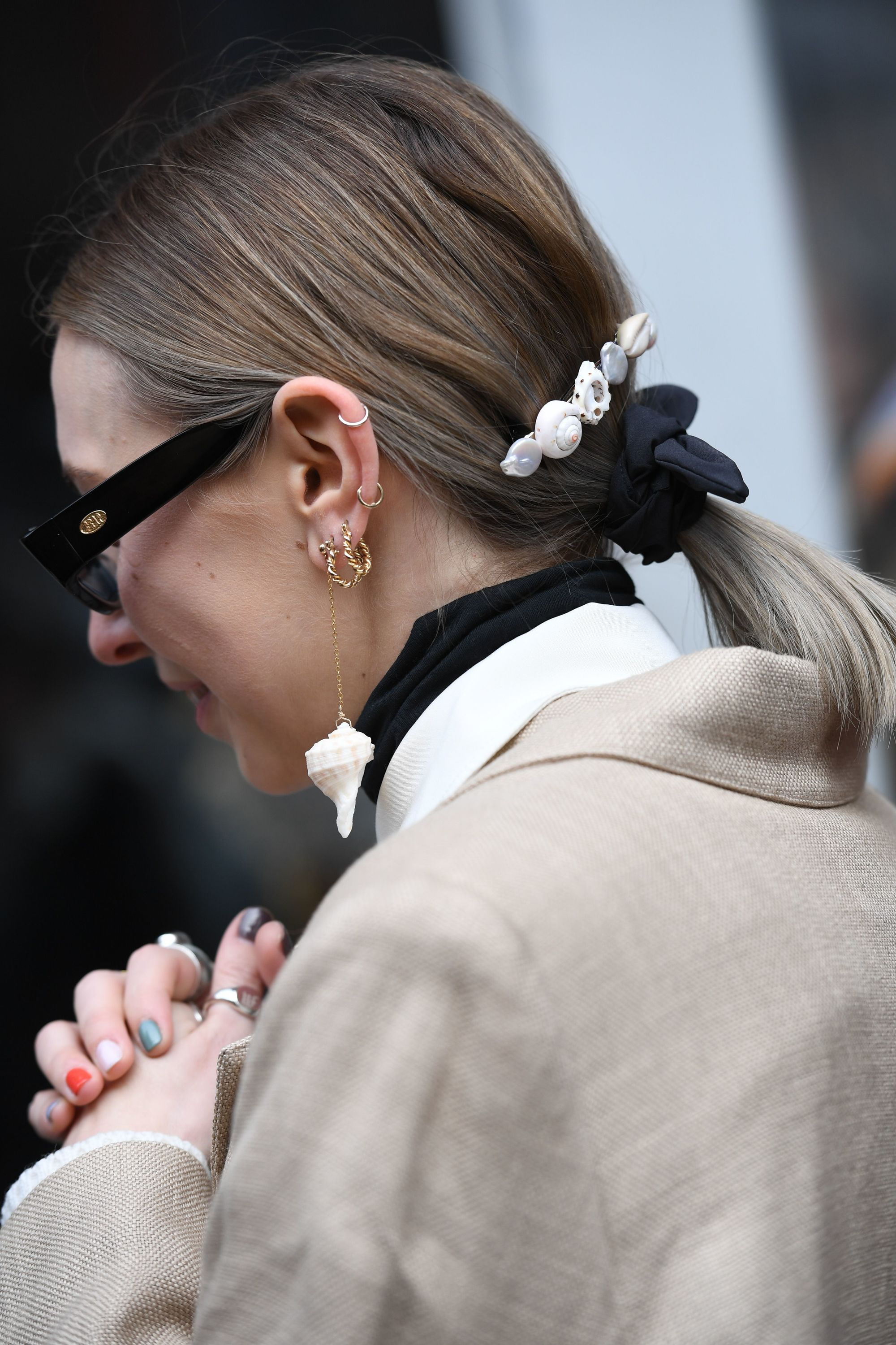 Side shot of woman with short dark to ash blonde hair styled into , wearing a beige coat