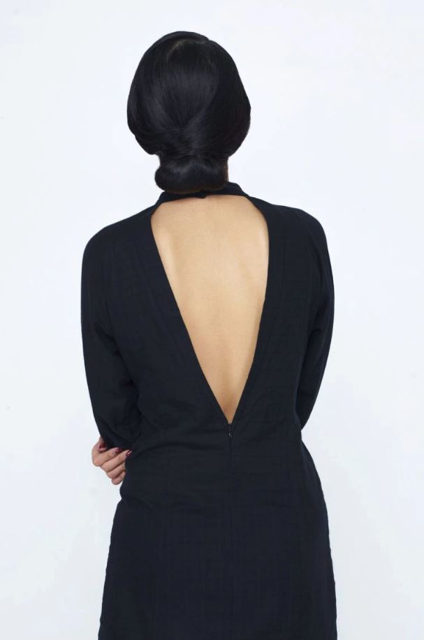 Chinese New Year hairstyles: Woman with straight dark brown hair in a chignon updo wearing a backless dress.