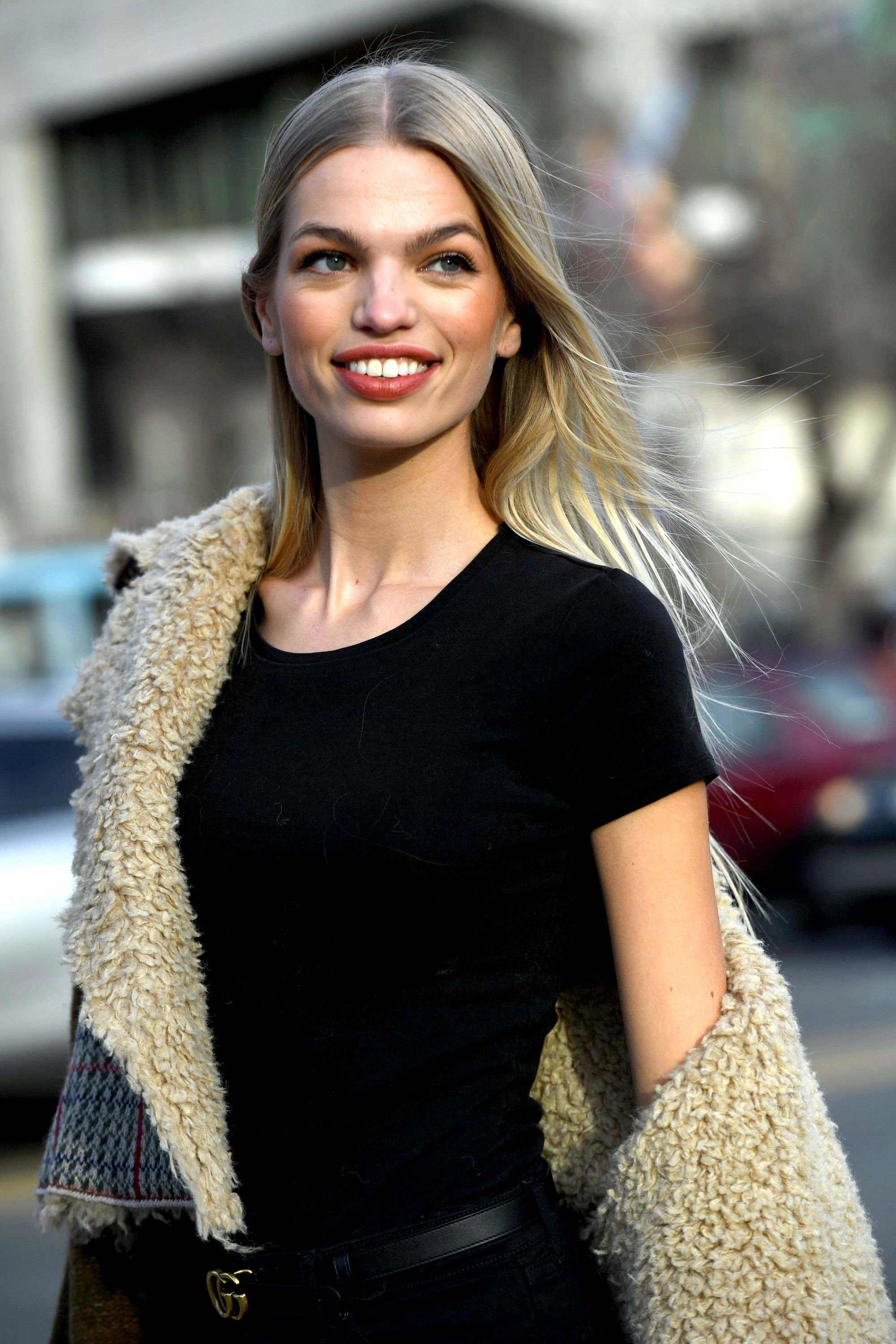 Shot of woman with long dark ash blonde hair with honey tones, wearing black shirt with borg jacket outside