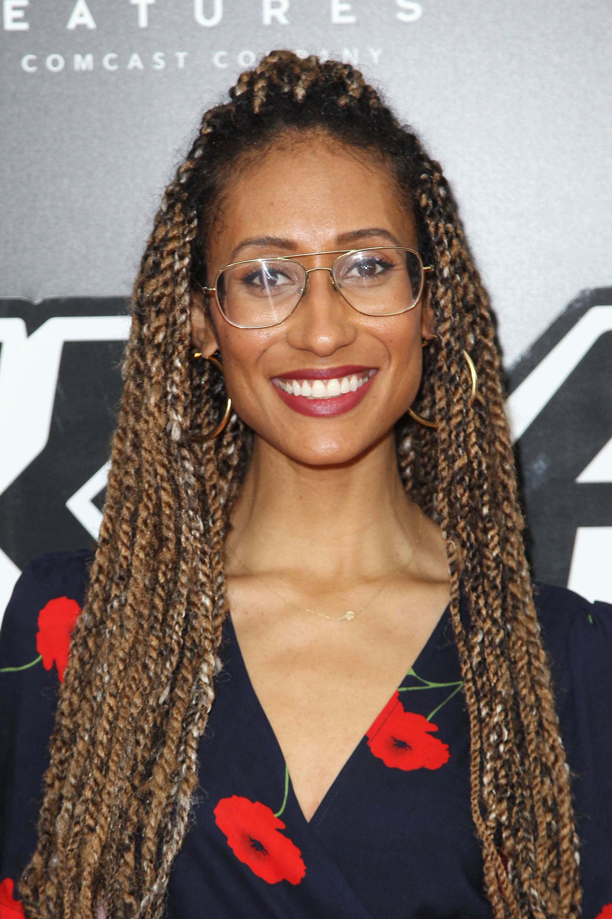 Elaine Welteroth with long caramel marley twists, wearing glasses with print black top with roses on the red carpet