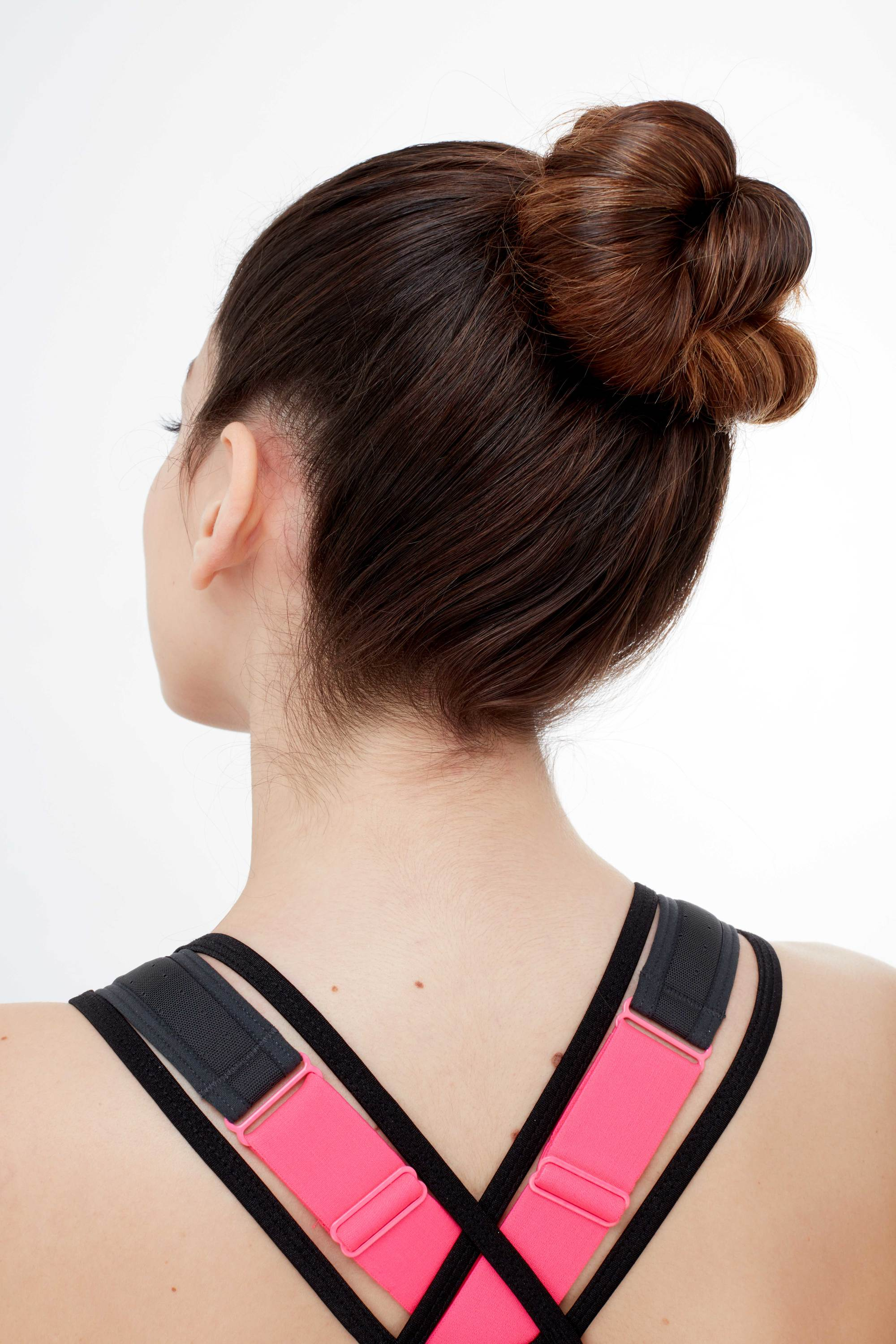 Gym hairstyles for thick hair: Back shot of a brunette model with a twisted high bun, wearing a sporty strappy top and sports bra