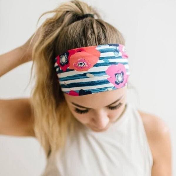 Gym hairstyles for thick hair: Picture of a woman with blonde hair in a high ponytail with a stripy and floral print headband