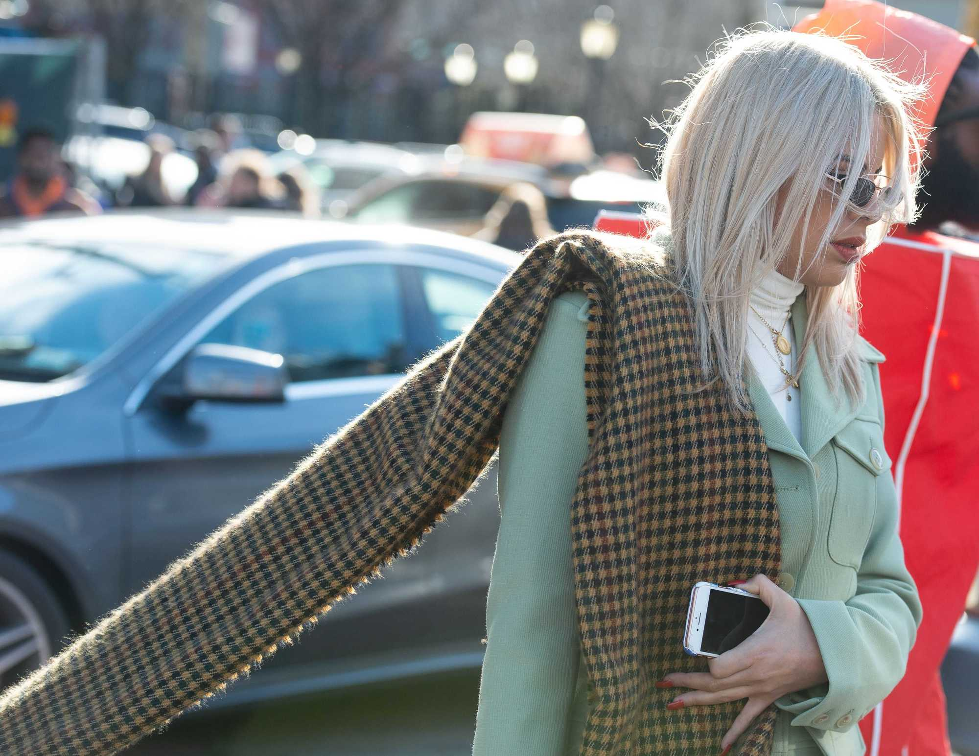 Woman on the street with shoulder length straight ash blonde hair, wearing plaid scarf with mint green blazer outside
