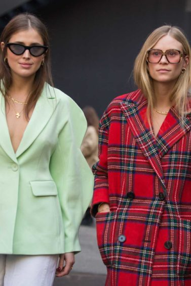 Milan Fashion Week FW18: Woman with brown straight hair wearing a light green jacket walking with a blonde woman wearing a red tartan coat, both women wearing sunglasses.
