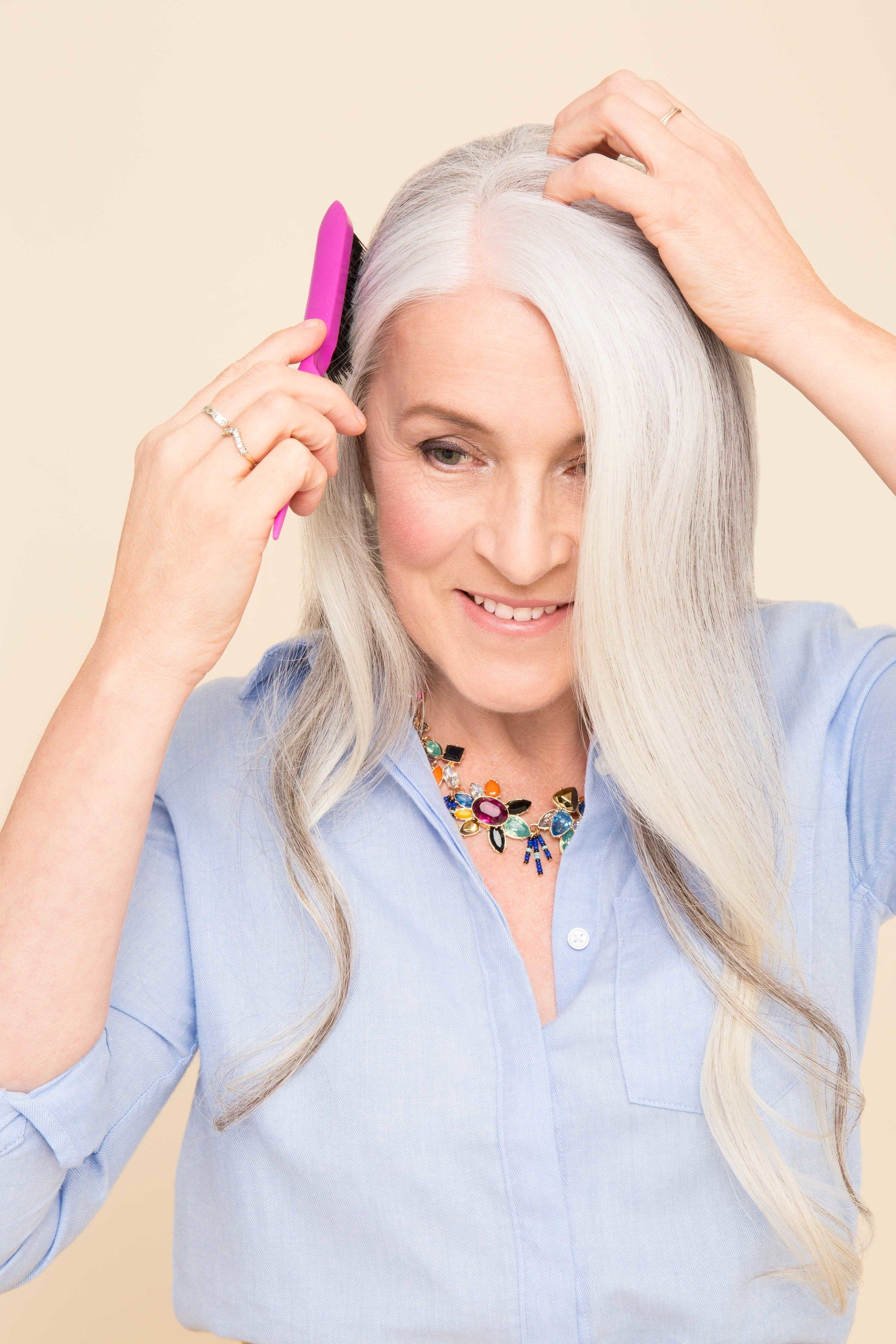 My hair is thinning: Older woman with long grey hair with soft curls, using a pink backcombing brush