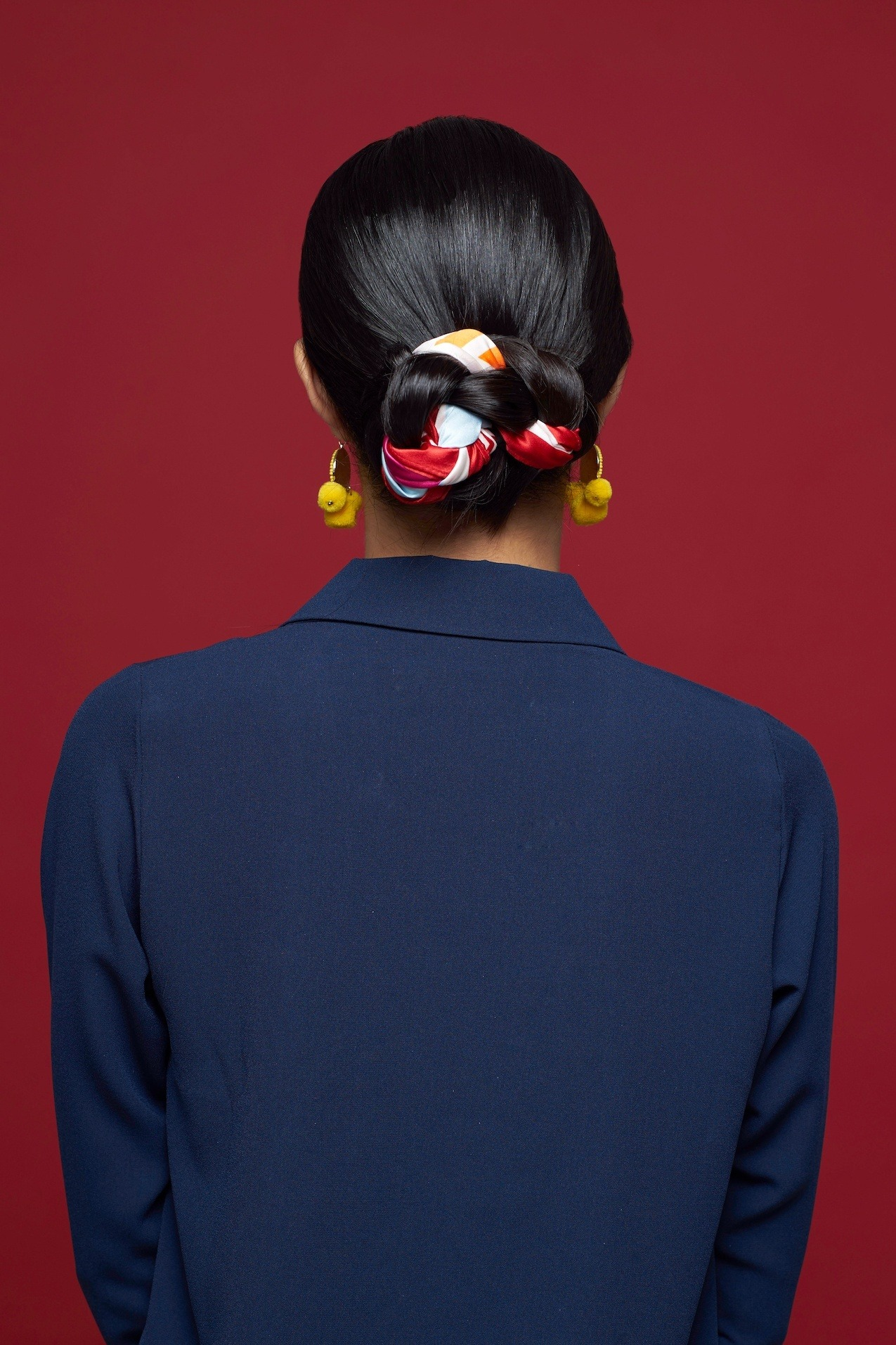 Chinese New Year hairstyles: Model with dark brown straight hair in low bun with scarf detail wearing a navy blazer jacket.