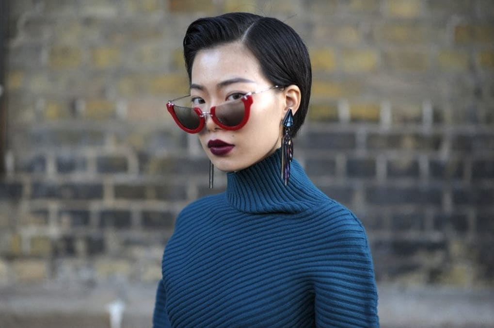 Chinese New Year hairstyles: Asian woman with short dark brown straight hair in sleek quiff bob wearing sunglasses and a turtleneck.