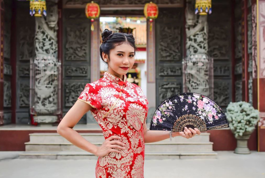 Chinese New Year hairstyles: Asian woman with straight hair in double space buns updo wearing traditional clothing.