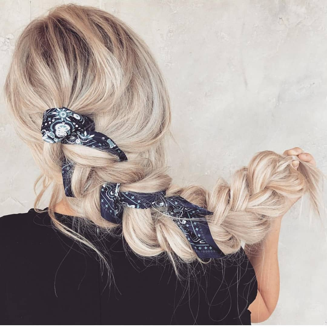 Bandana hairstyles: Woman with bleach blonde hair styled into a pull-through braid with a blue bandana in it