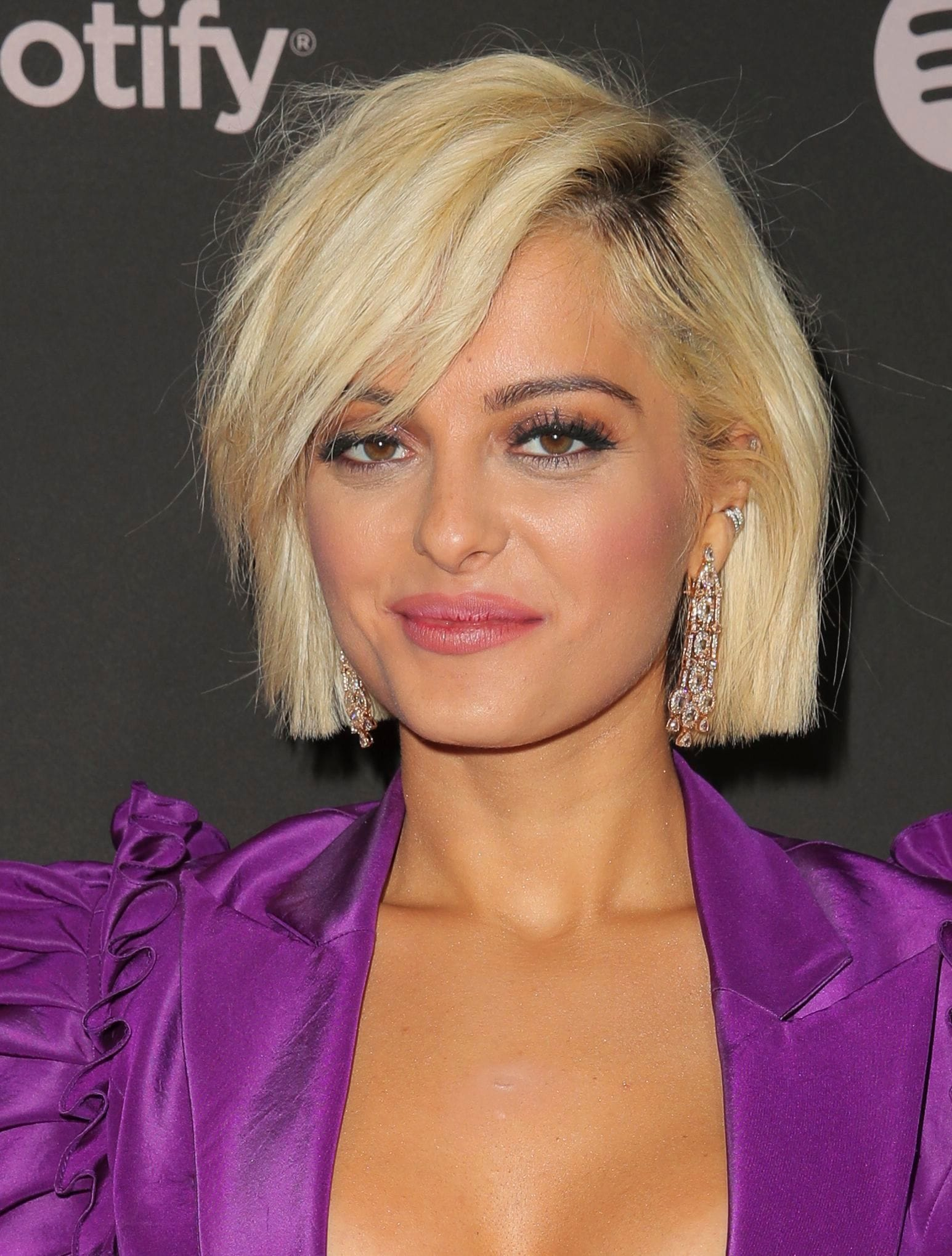 Bebe Rexha with a short golden blonde bob haircut with long side fringe