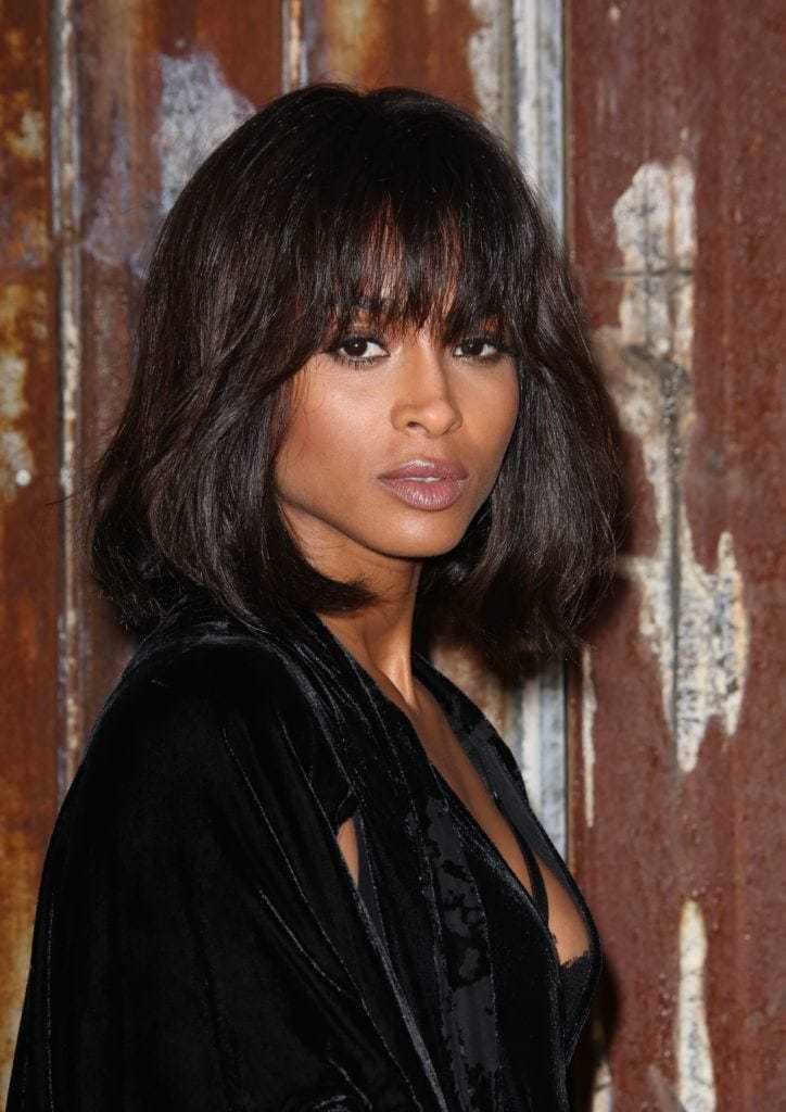 Modern bob hairstyles: Ciara with dark long bob with thick straight bangs, wearing black on the red carpet