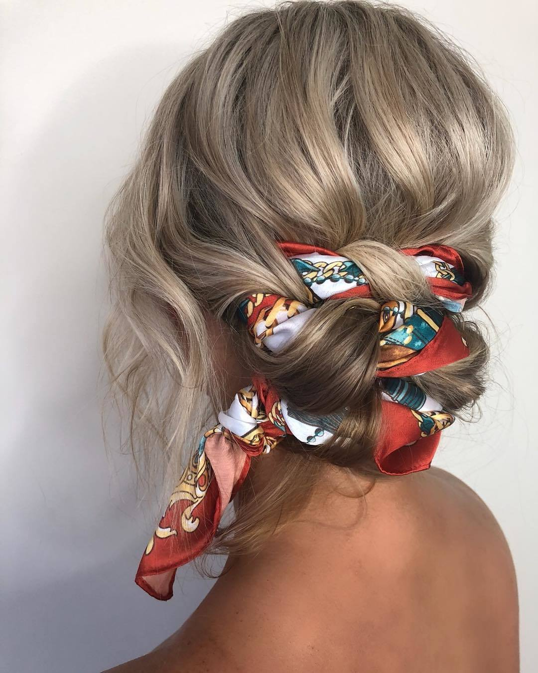 Bandana hairstyles: Woman with ash blonde wavy hair styled into a braided bun with a bandana weaved into it