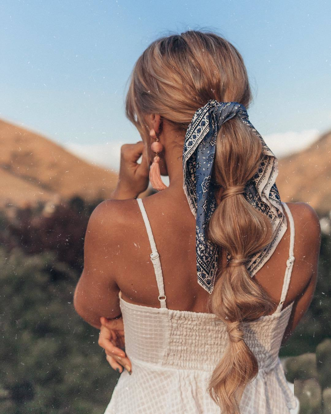 Bandana hairstyles: Woman with honey blonde long hair styled into a bubble ponytail with bandana around it