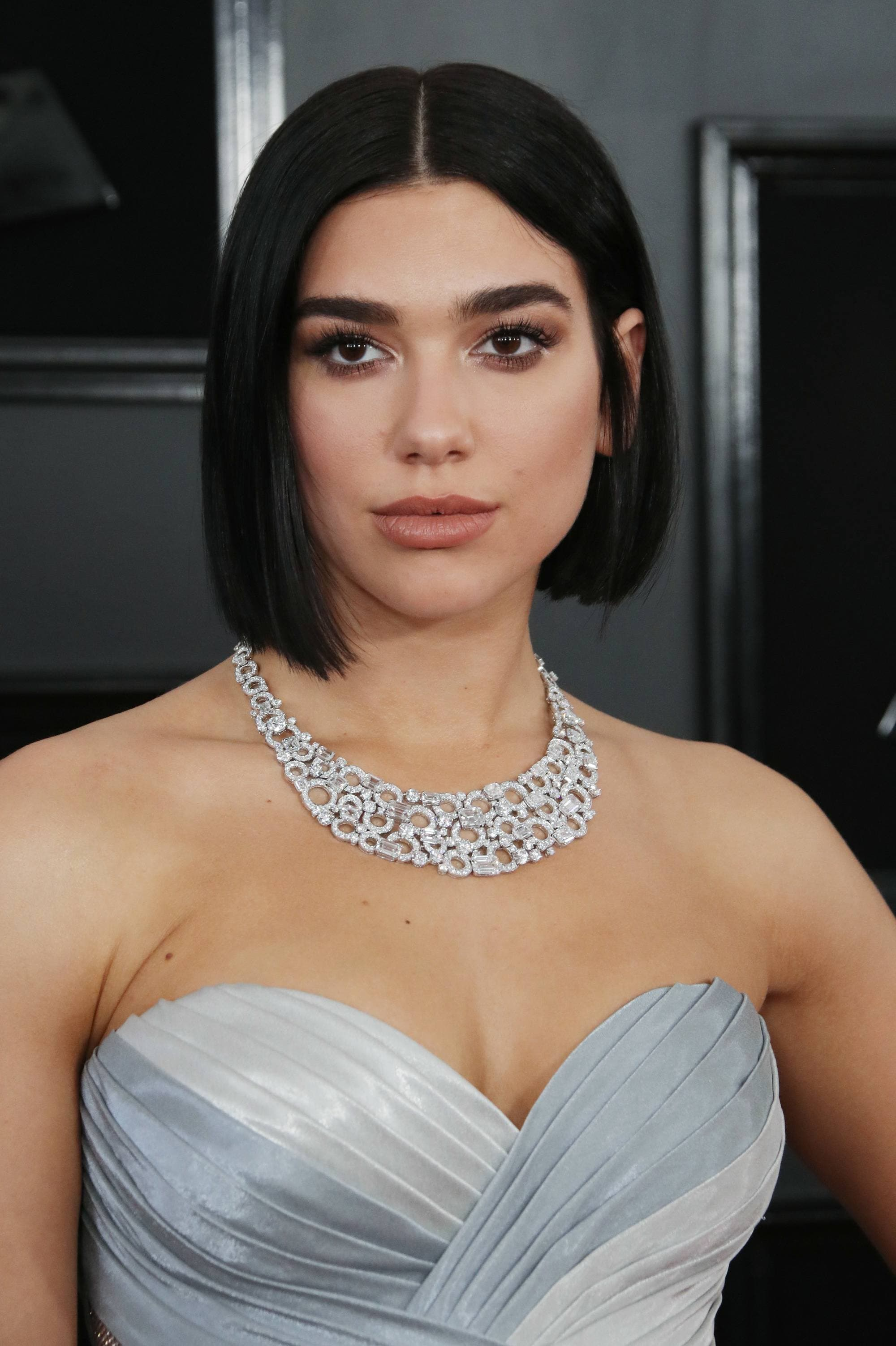 Dua Lipa with a blunt bob haircut, wearing necklace with low cut silver dress