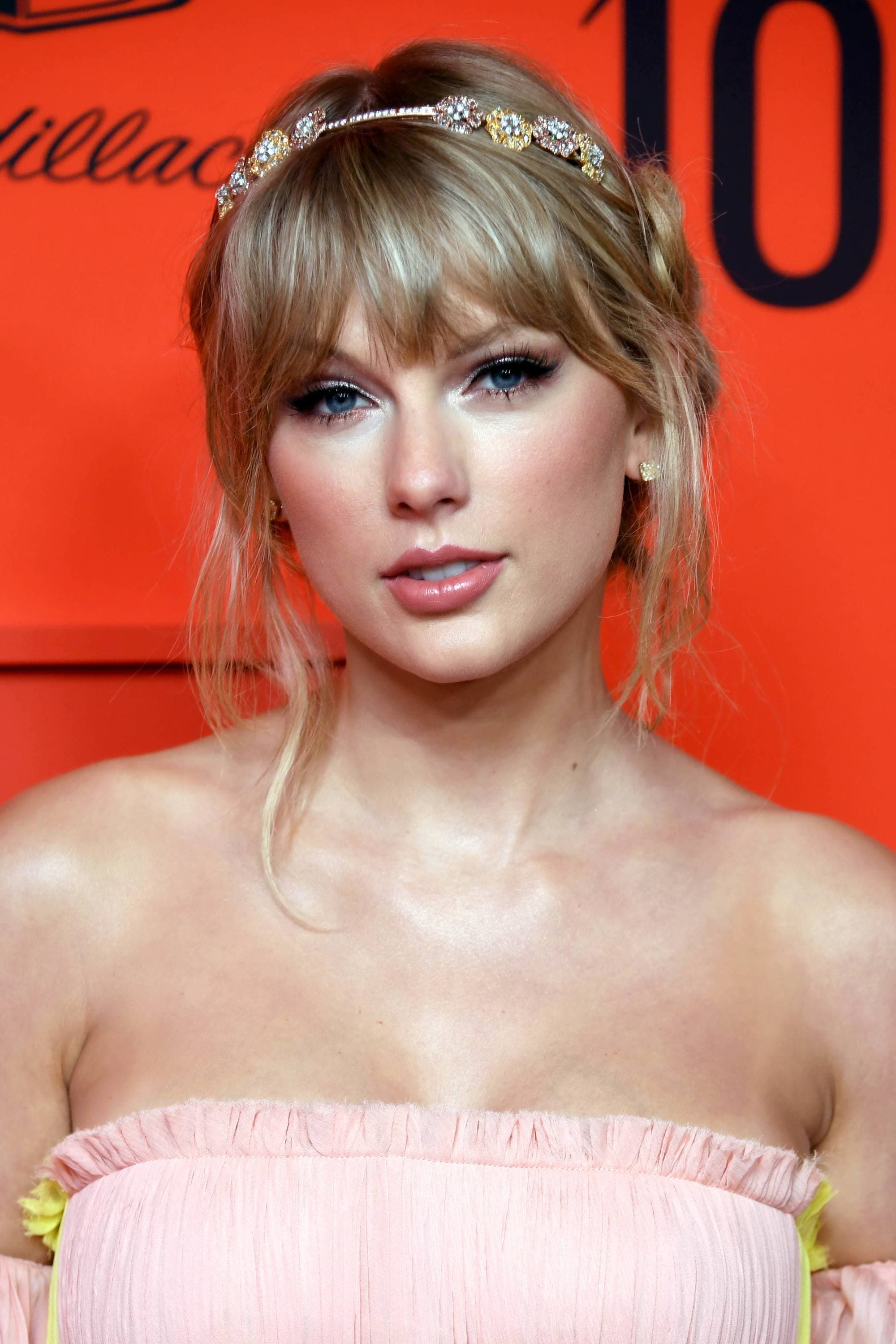 Headband hairstyles: Taylor Swift with halo braid with wispy bangs with a floral headband on, wearing pink dress at the Time 100 Gala event