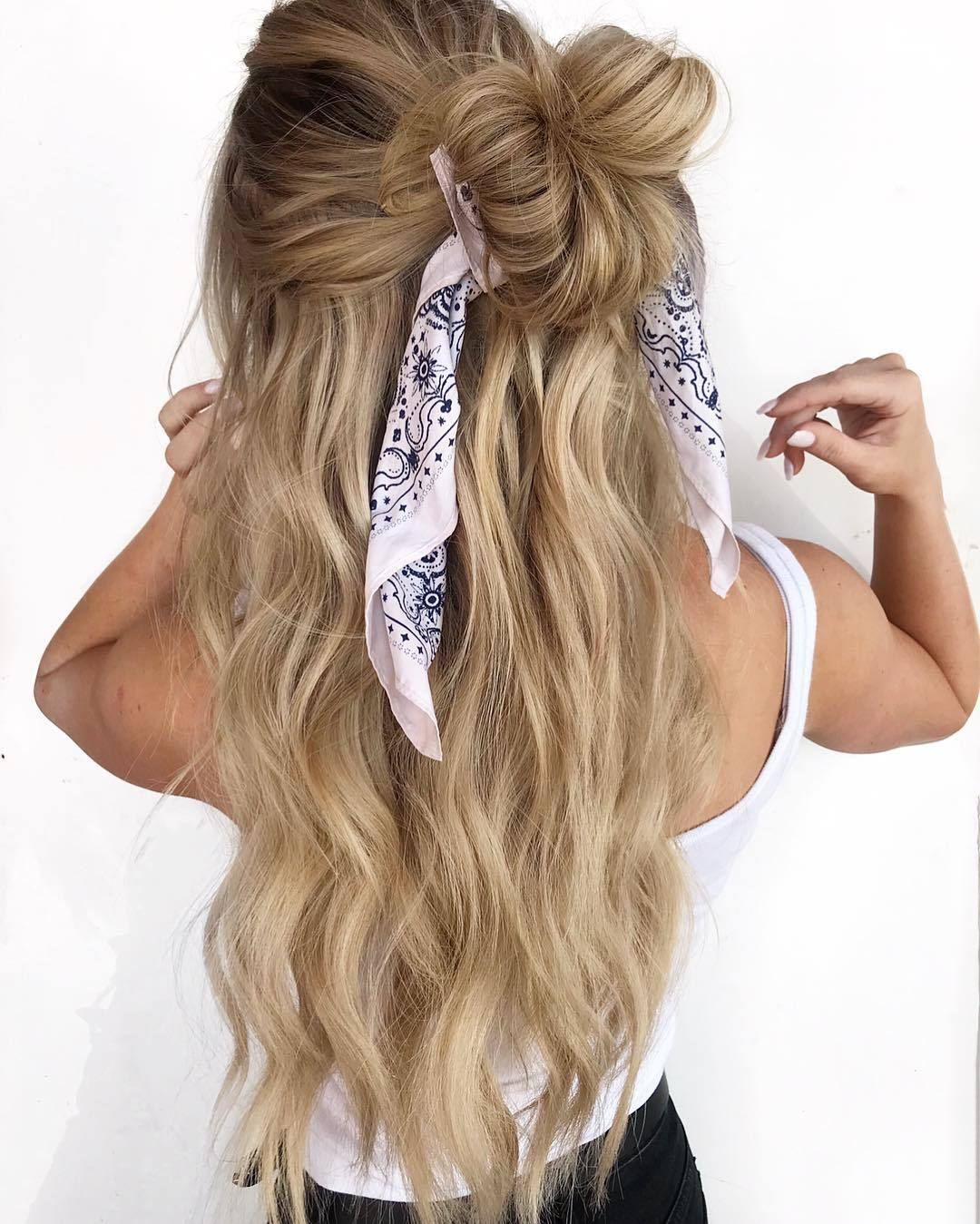 Bandana hairstyles: Woman with long dirty blonde hair styled into a half-up, half-down bun with a bandana wrapped around it