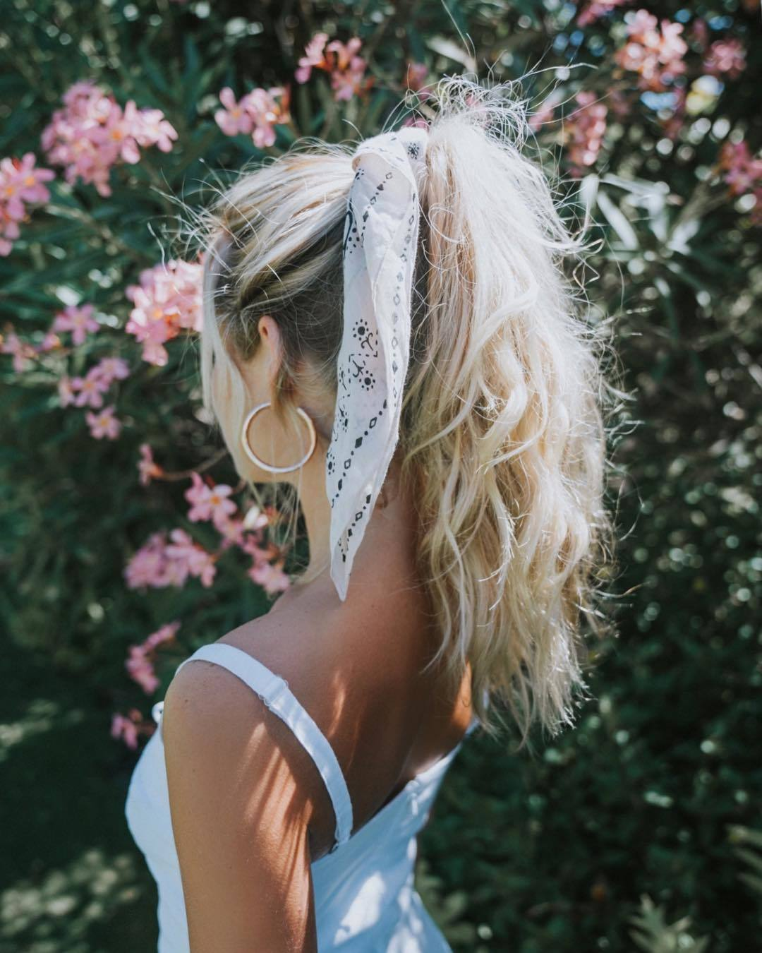 Bandana hairstyles: Woman with long bleach blonde messy hair styled into a high ponytail with a bandana tied around it, posing against flowers