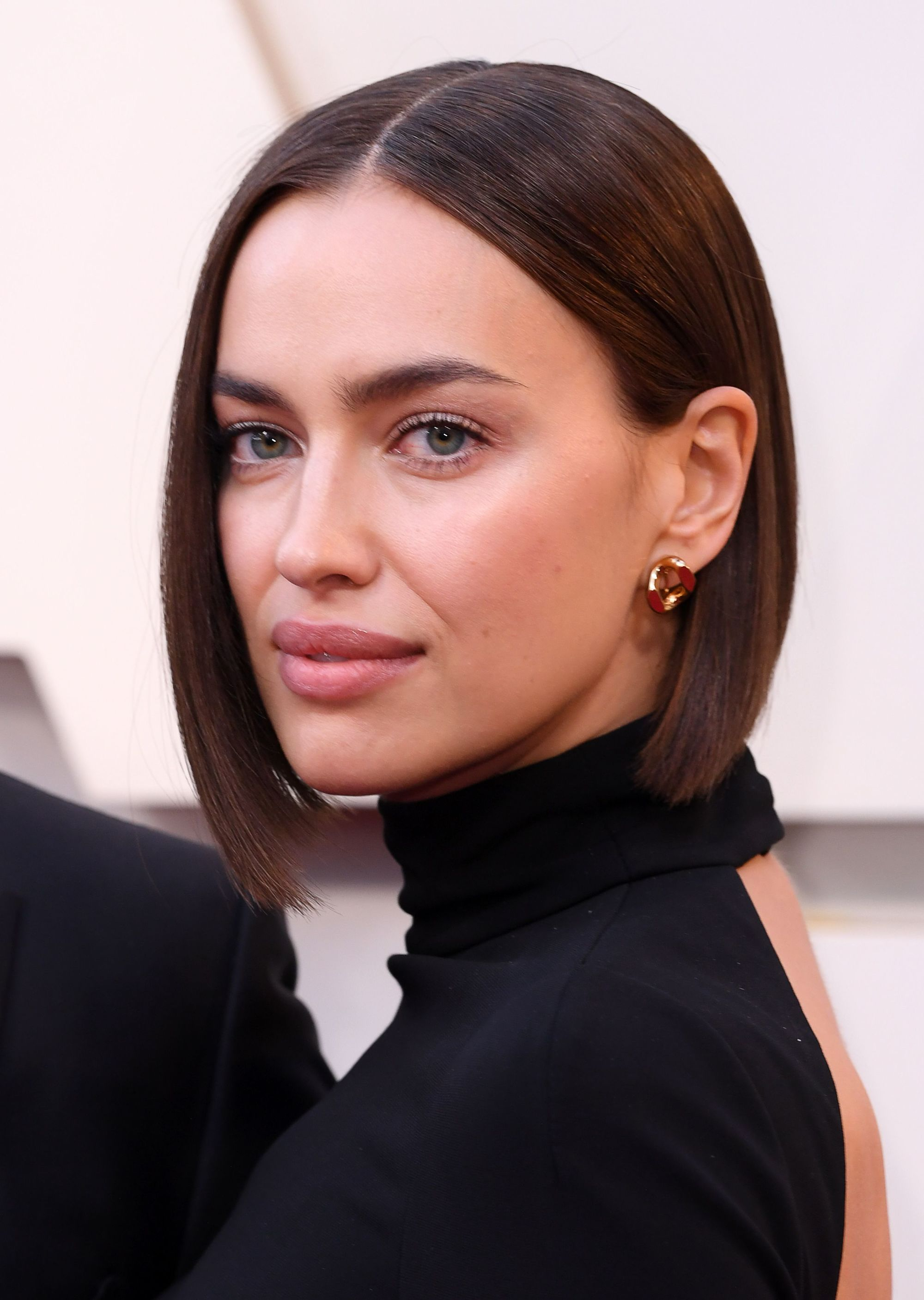 Spring haircuts: Irina Shayk at the Oscars with a short blunt dark brunette bob, wearing a high neck backless black dress