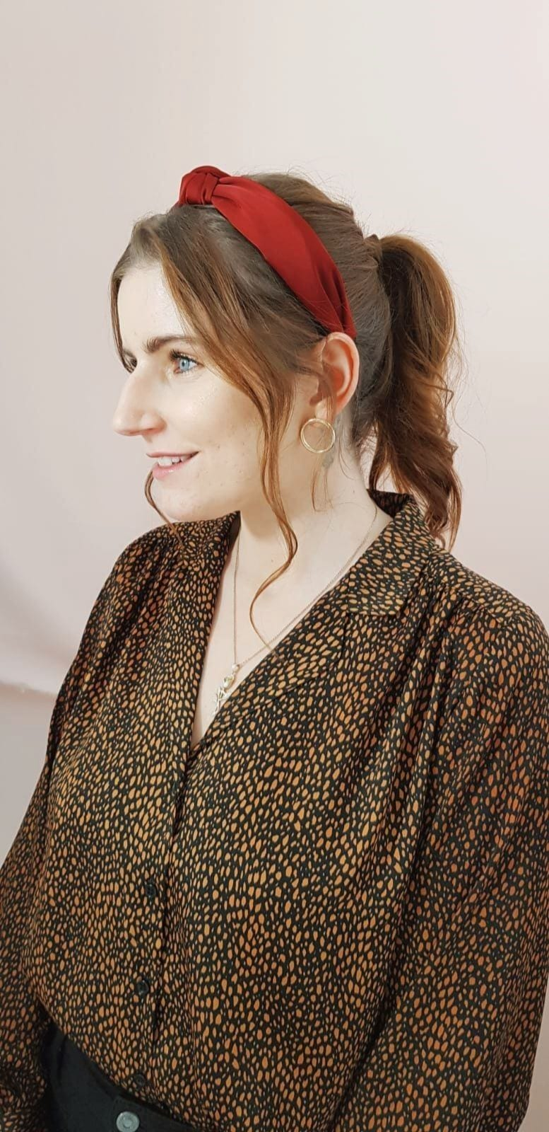 Trend on trial: Woman with brown wavy hair in ponytail wearing a burgundy knotted headband and pattern shirt.