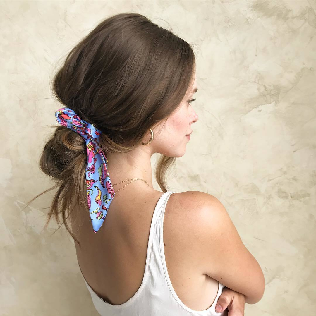 Bandana hairstyles: Woman with medium brown hair styled into a low bun with a bandana wrapped around it