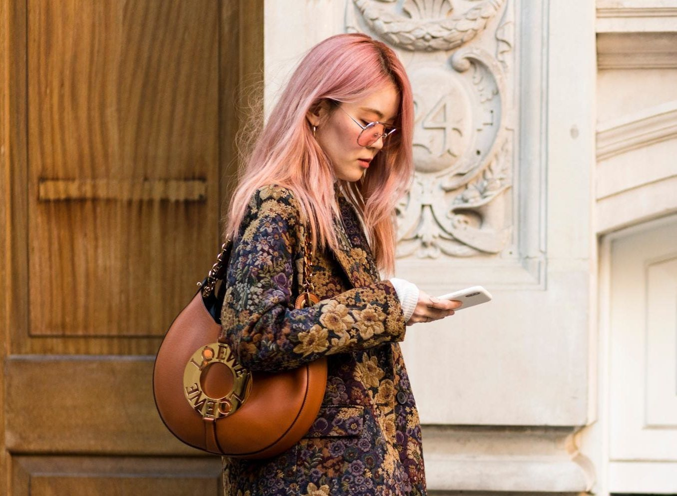 Woman with long straight pastel pink hair wearing sunglasses and '70s-inspired outfit at London Fashion Week.