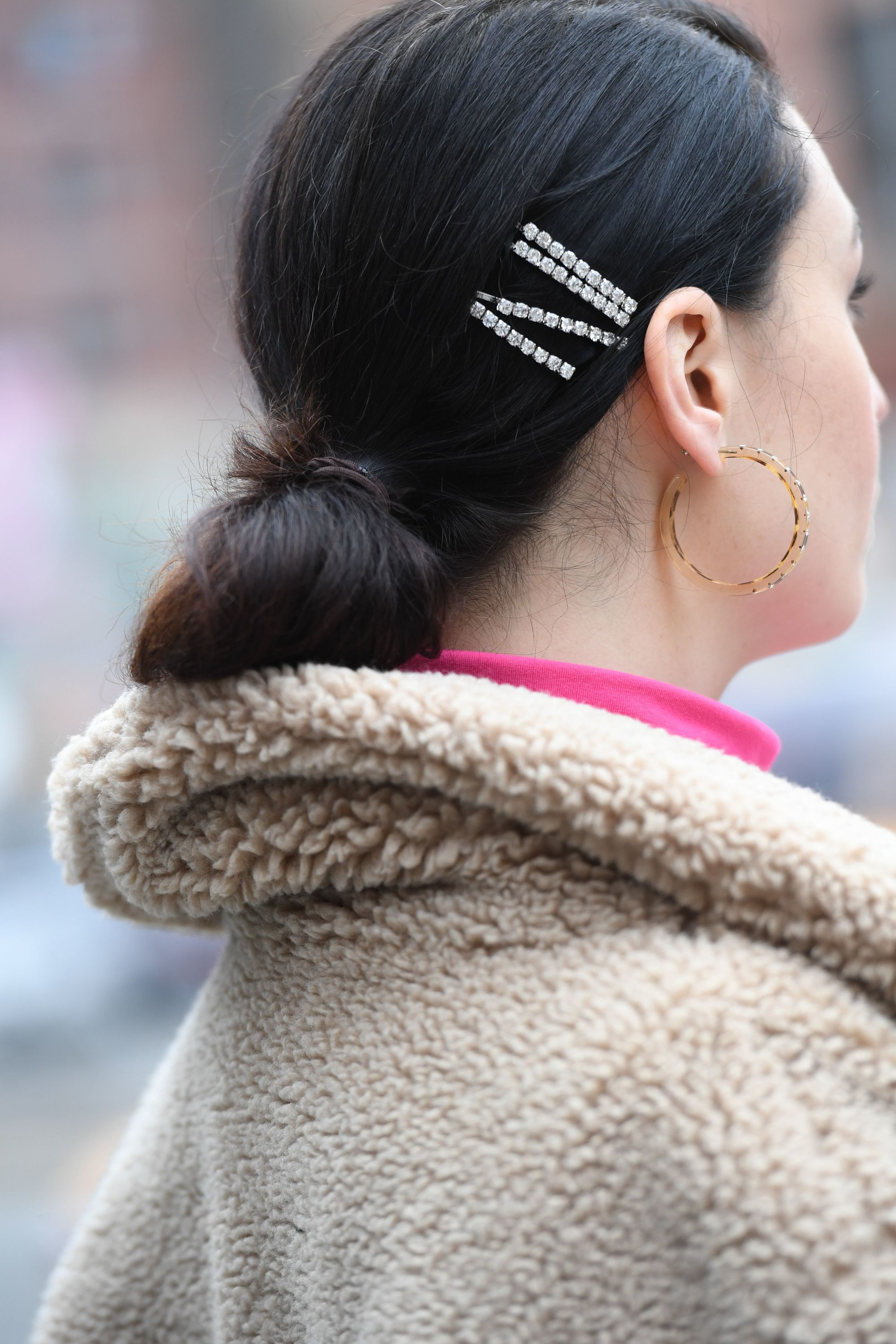 Diamante hair trend: Back side view photo of a street styler with dark hair in a low bun with four diamante encrusted hair slides