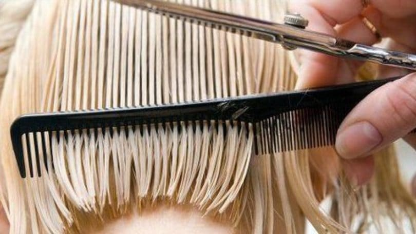 close up of a comb in blonde hair with scissors