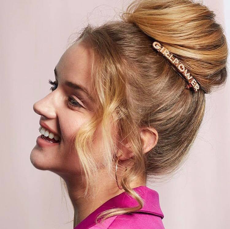 TRESemmé #PowerYourPresence: Shot of a woman with a golden blonde hair styled into a high ballerina bun, wearing a girl power slide with pink jacket in the All Things Hair Studio