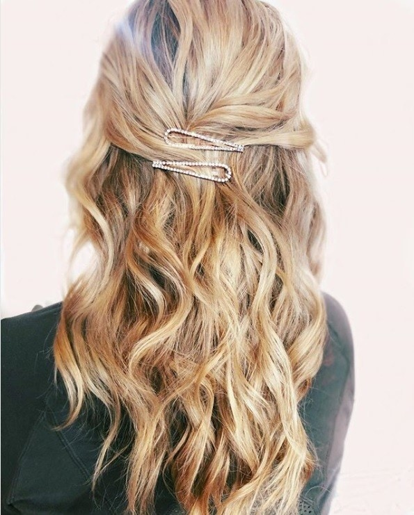 Diamante hair trend: Back view of a blonde woman with long curled hair in a half-up half-down hairstyle with diamante hair clips