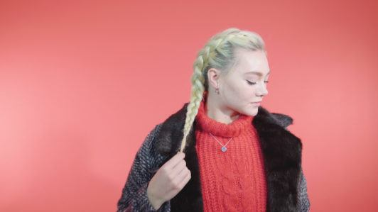 Side Dutch braid tutorial: Blonde girl with a side Dutch braid, wearing a red knit jumper and a coat