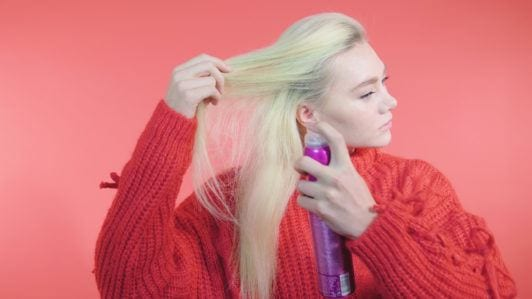 Side Dutch braid tutorial: Blonde girl with long straight hair spraying volumising spray into her roots, wearing a red knit jumper