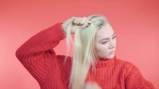 Side Dutch braid tutorial: Blonde girl with long straight hair dividing a section of hair into 3 to braid, wearing a red knit jumper