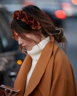 Bank holiday hairstyles: Woman with brown balayage wavy hair in messy low bun wearing a plaited headband and winter outfit.