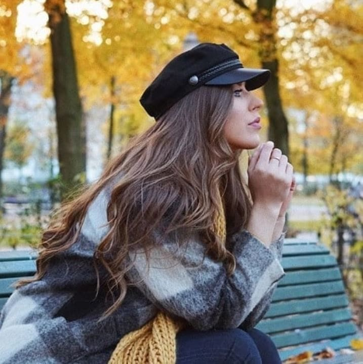 Bank holiday hairstyles: Woman with long wavy brown hair wearing a baker boy hat sitting on a bench.