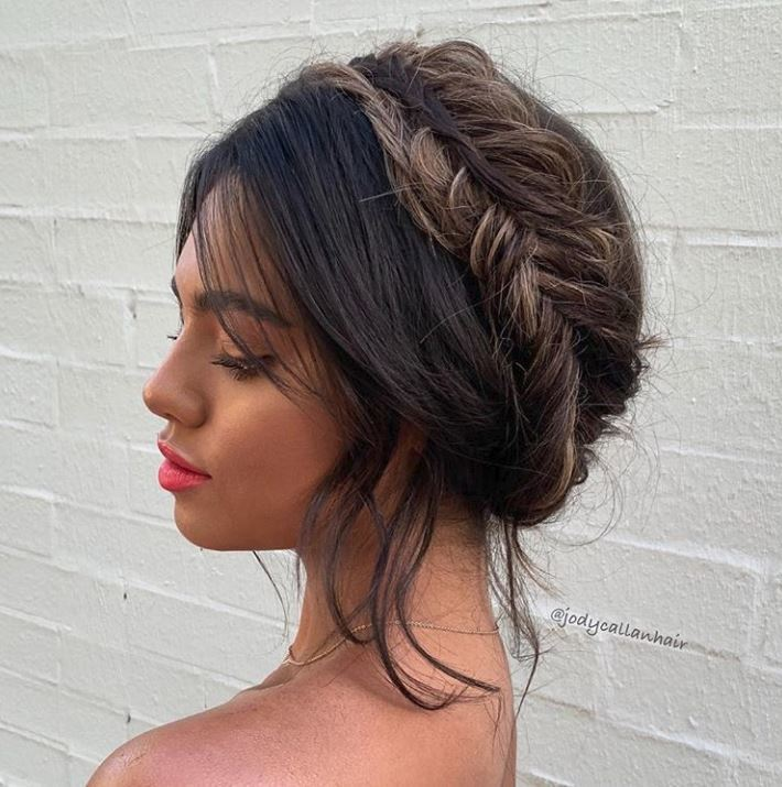 Bank holiday hairstyles: Woman with brown balayage wavy hair in fishtail milkmaid braids.