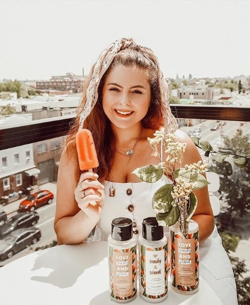 Photo of a woman with long brunette hair holding an ice lolly, her hair tied up with a scarf, with Love Beauty And Planet bottles used as a vase for flowers