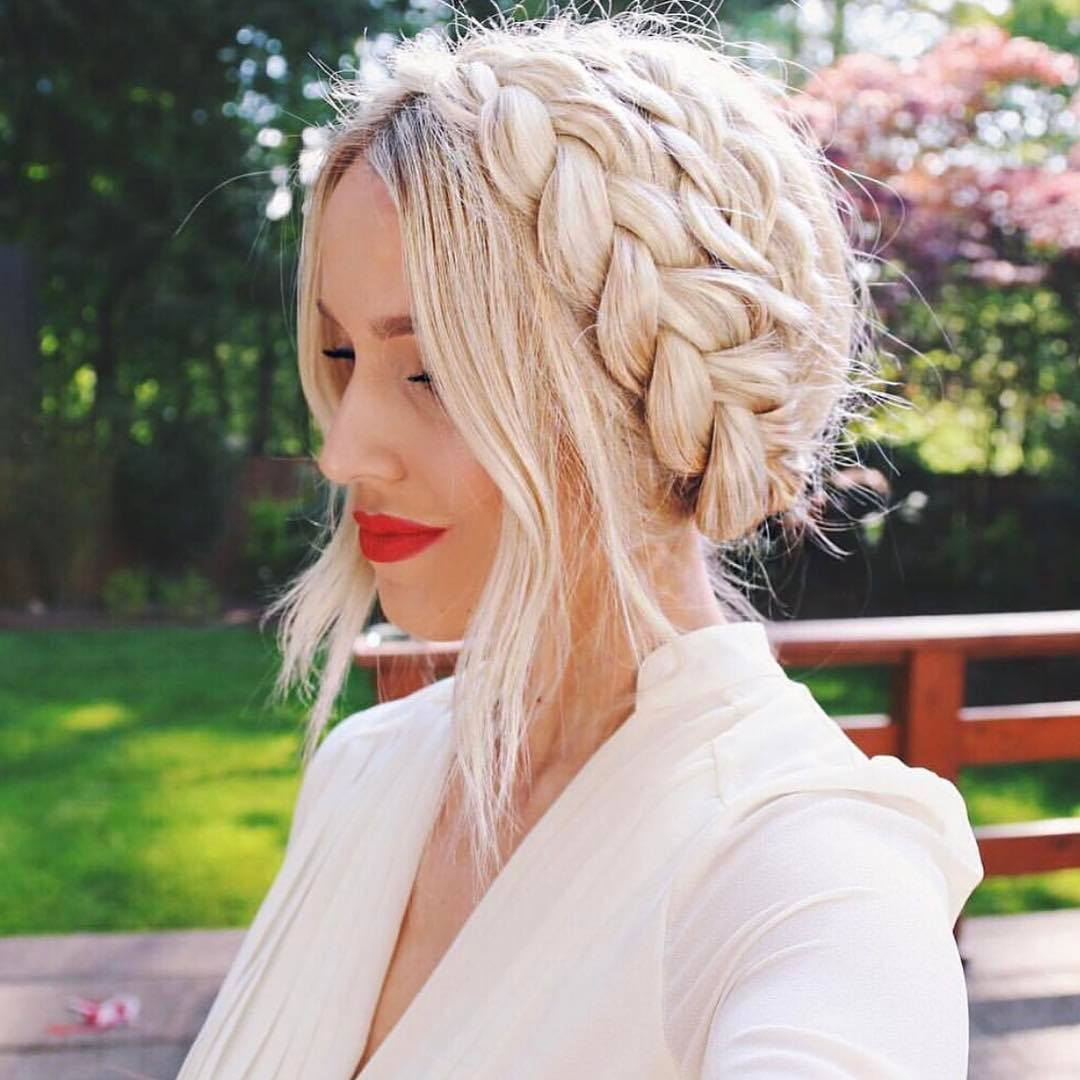 Wedding hairstyles: Woman with milkmaid braid with loose tendrils at the front, wearing a white wedding suit while posing outside