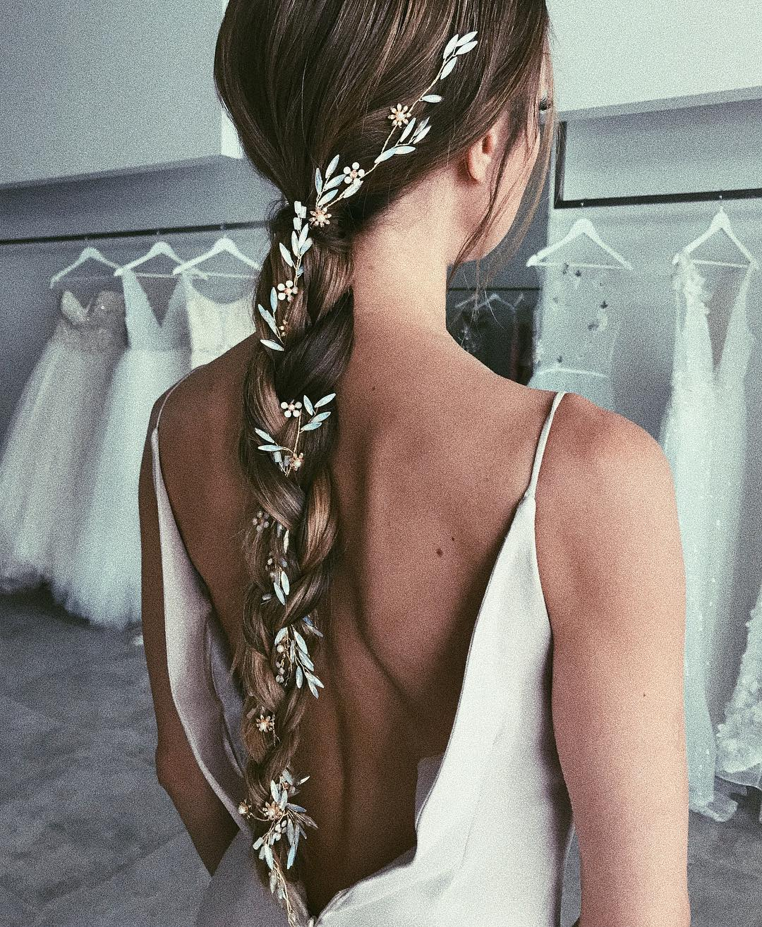 Wedding hair ideas: Shot of woman with dark brown long braided plait with flowers in it, wearing a wedding dress in bridal showroom