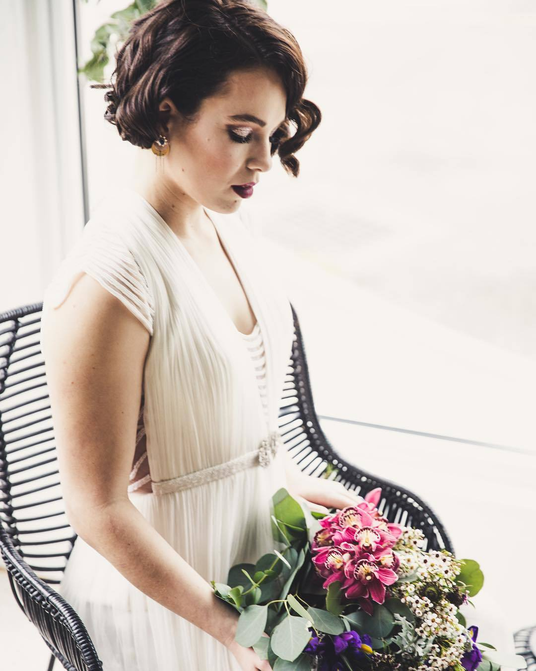 Vintage wedding hairstyles: Woman with short hair styled into retro curls, wearing a dress and holding flowers
