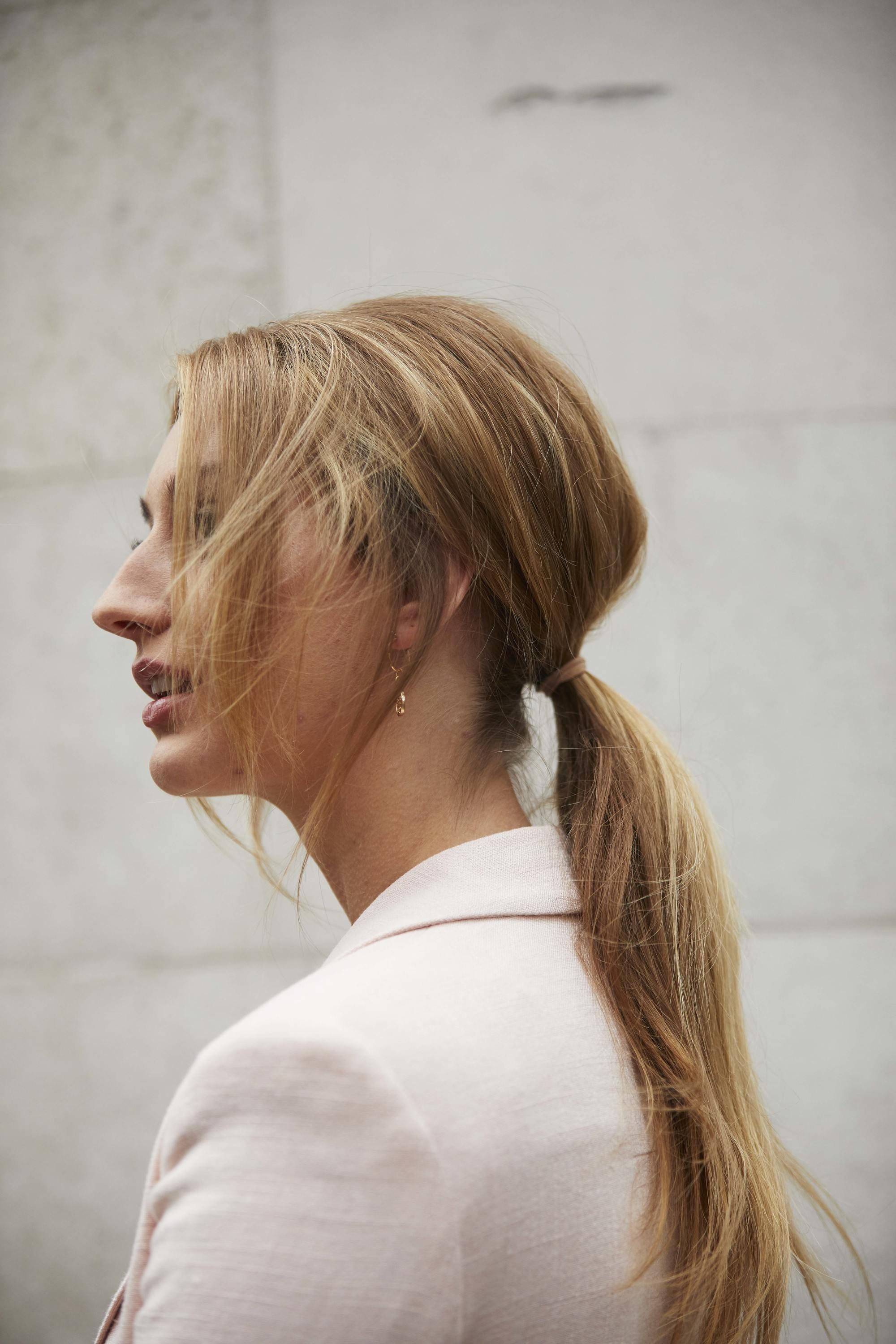 Bridesmaid hairstyles: Woman with golden blonde long hair styled into a ponytail