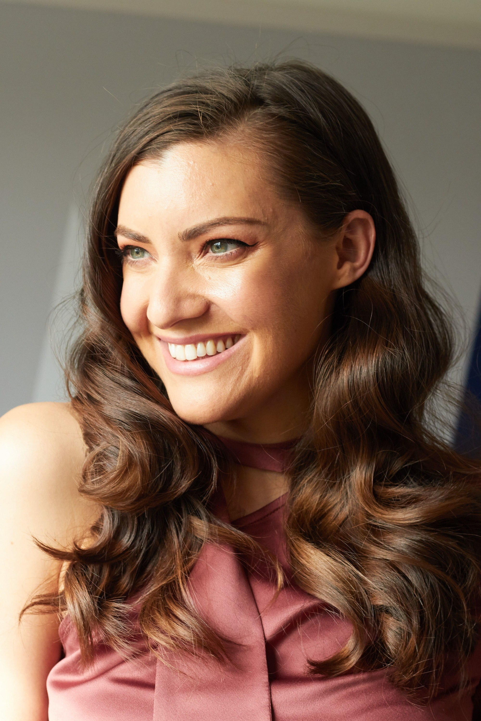 Bridesmaid hairstyles: Woman with dark brown hair styled into retro curls smiling