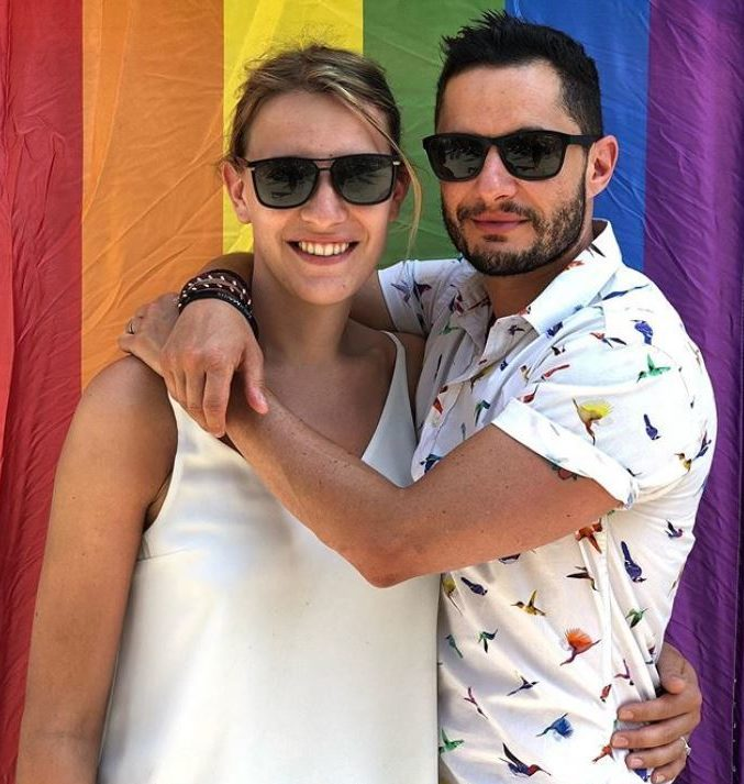 Hannah and Jake Graf hugging in front of a Pride flag