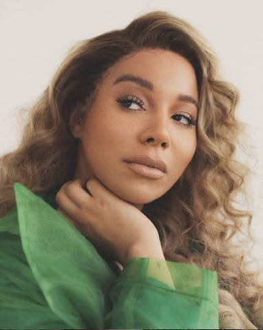 Munroe Bergdorf with light caramel curly hair.