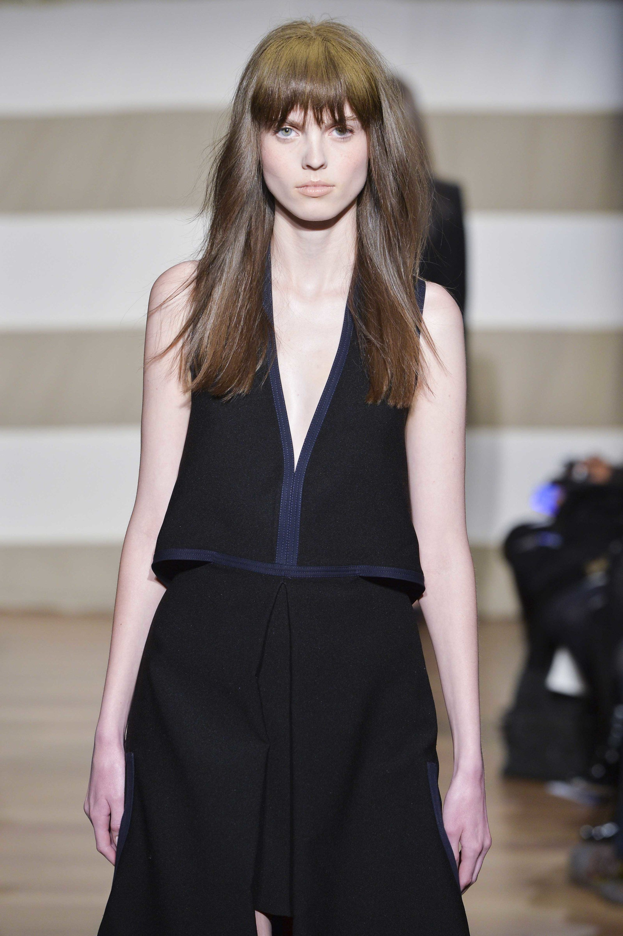 Hair color for morenas: Woman with long ash brown hair with bangs wearing a black outfit on the runway