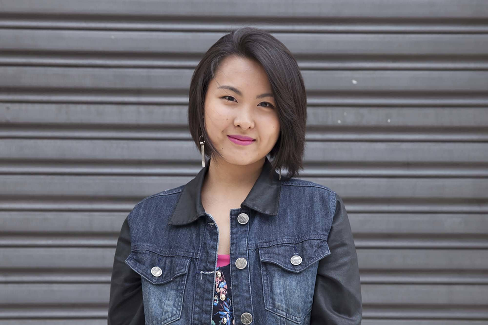 asian with black side swept bob in a denim jacket