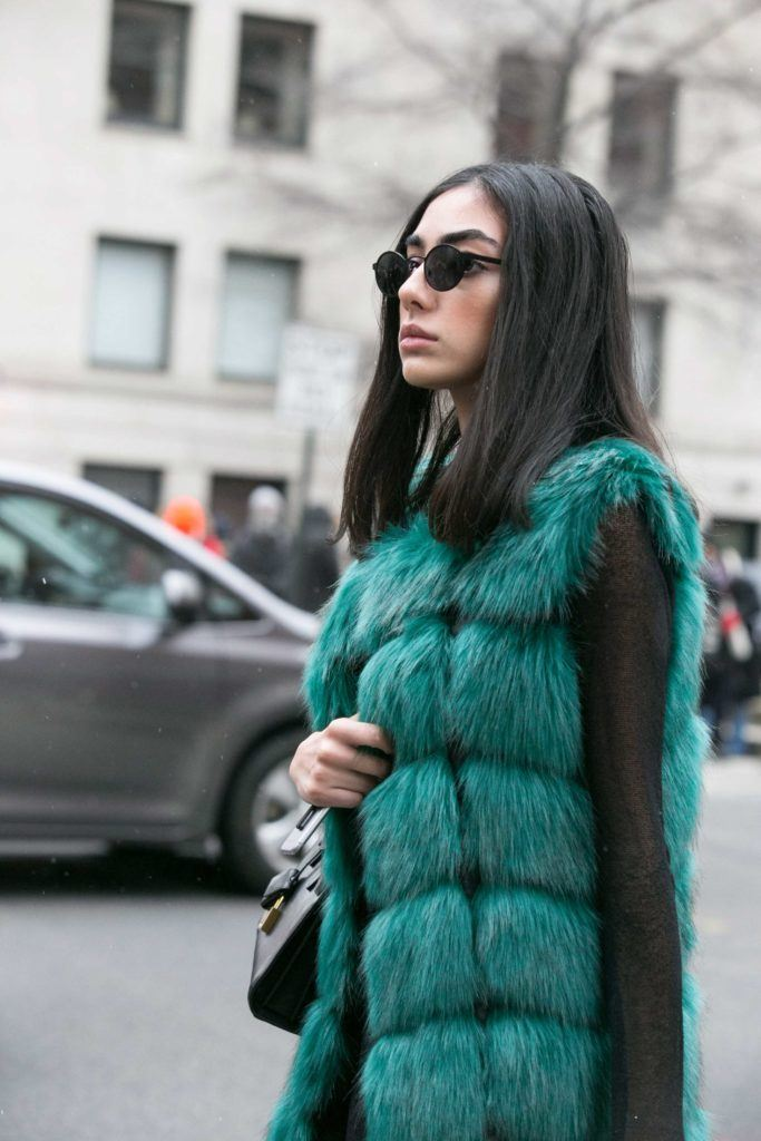 street style shot of asian woman with sleek and straight shoulder length haircut with faux fur coat straight hair