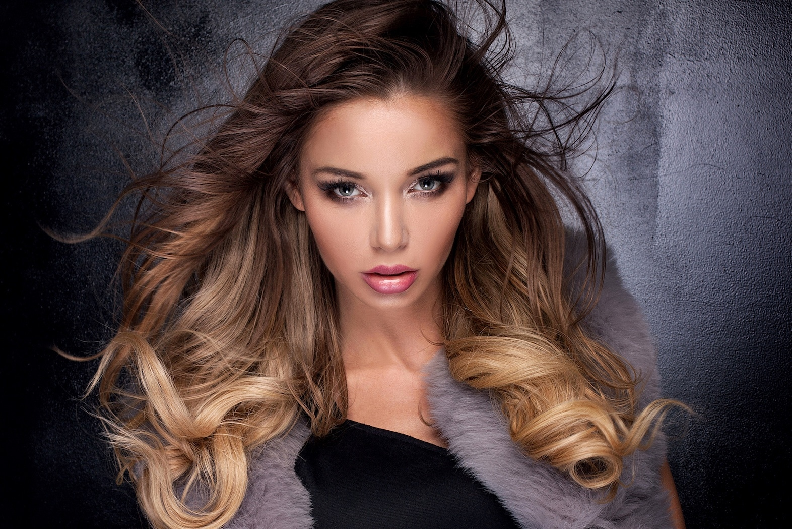 Hair color for morenas: Woman with long ombre bronde hair wearing a gray coat