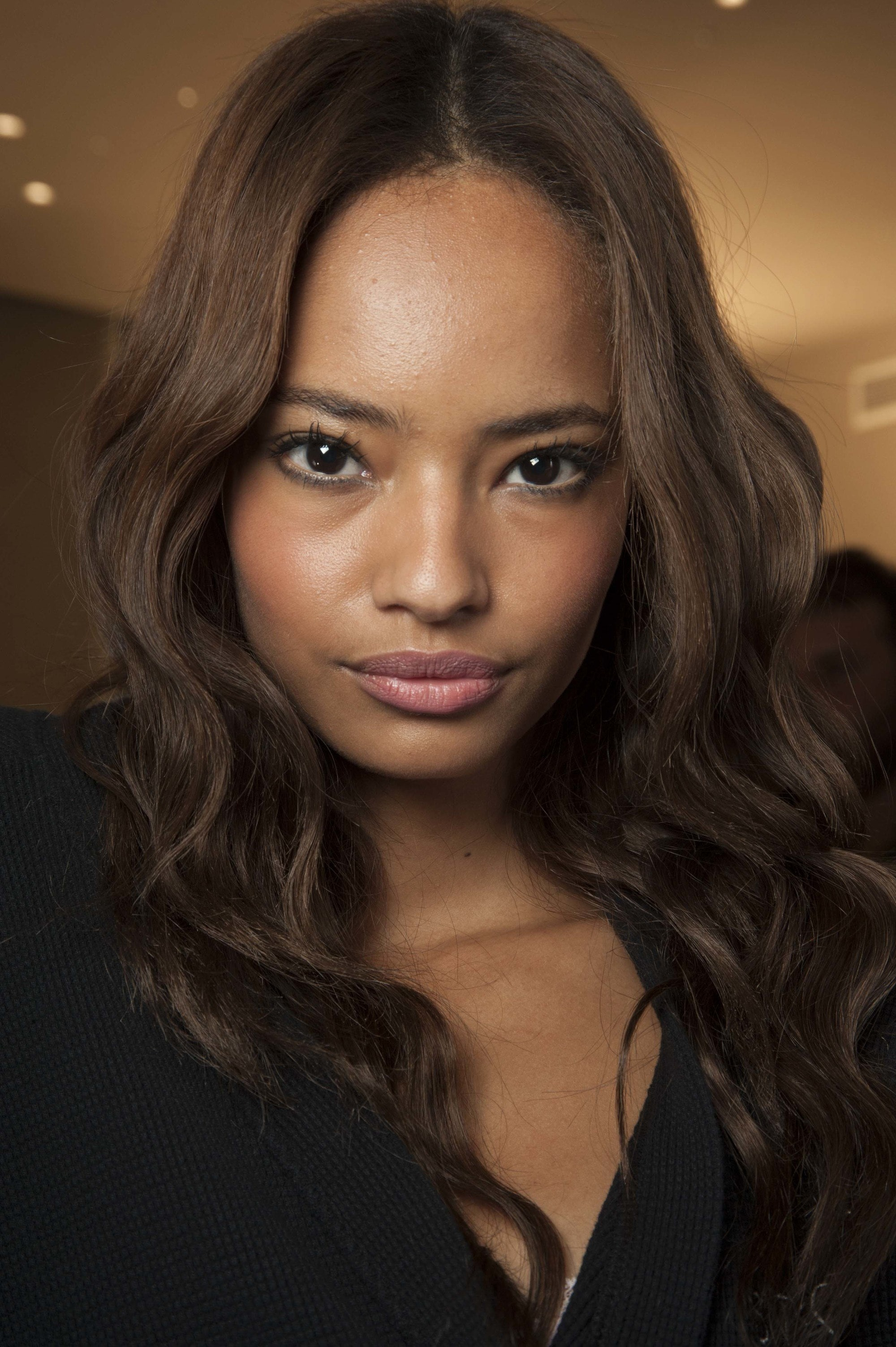 Hair colors for morena: Closeup shot of a woman with brown skin and long espresso hair