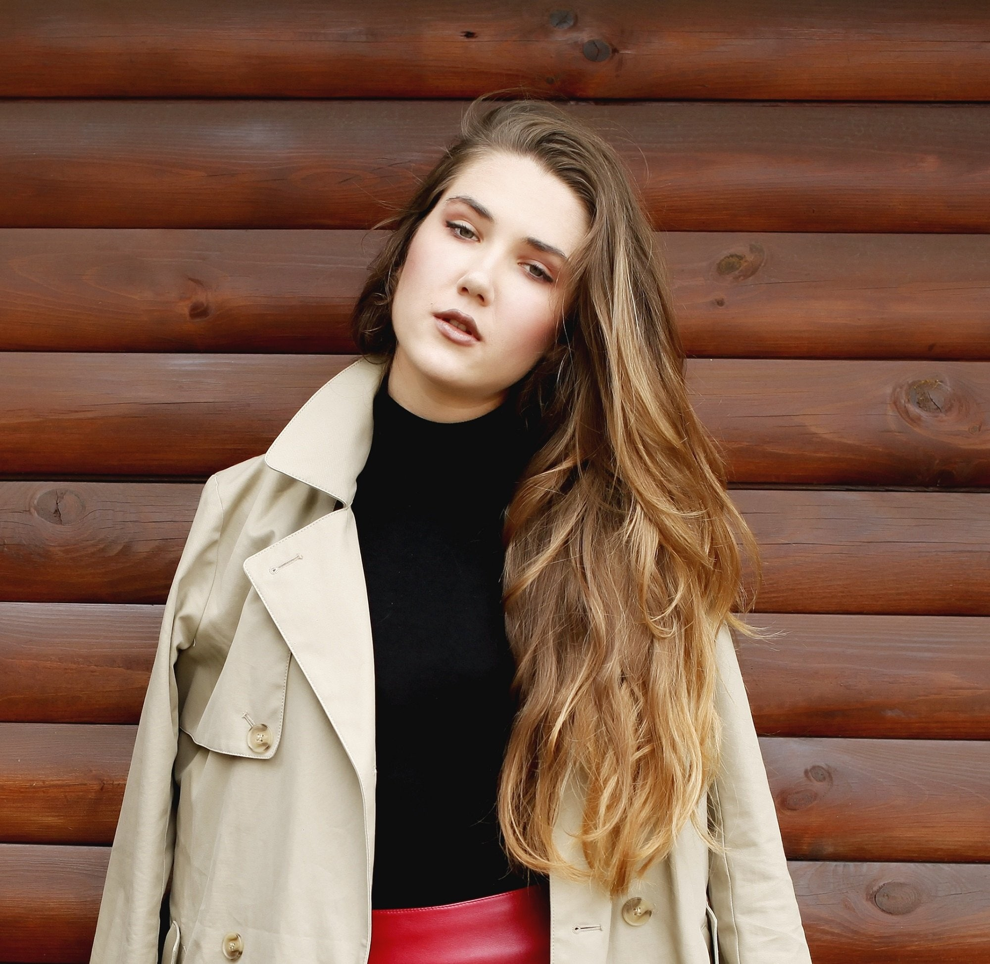 Hair color for fair skin: White woman with long bronde ombre hair wearing a coat against a wooden wall outdoors
