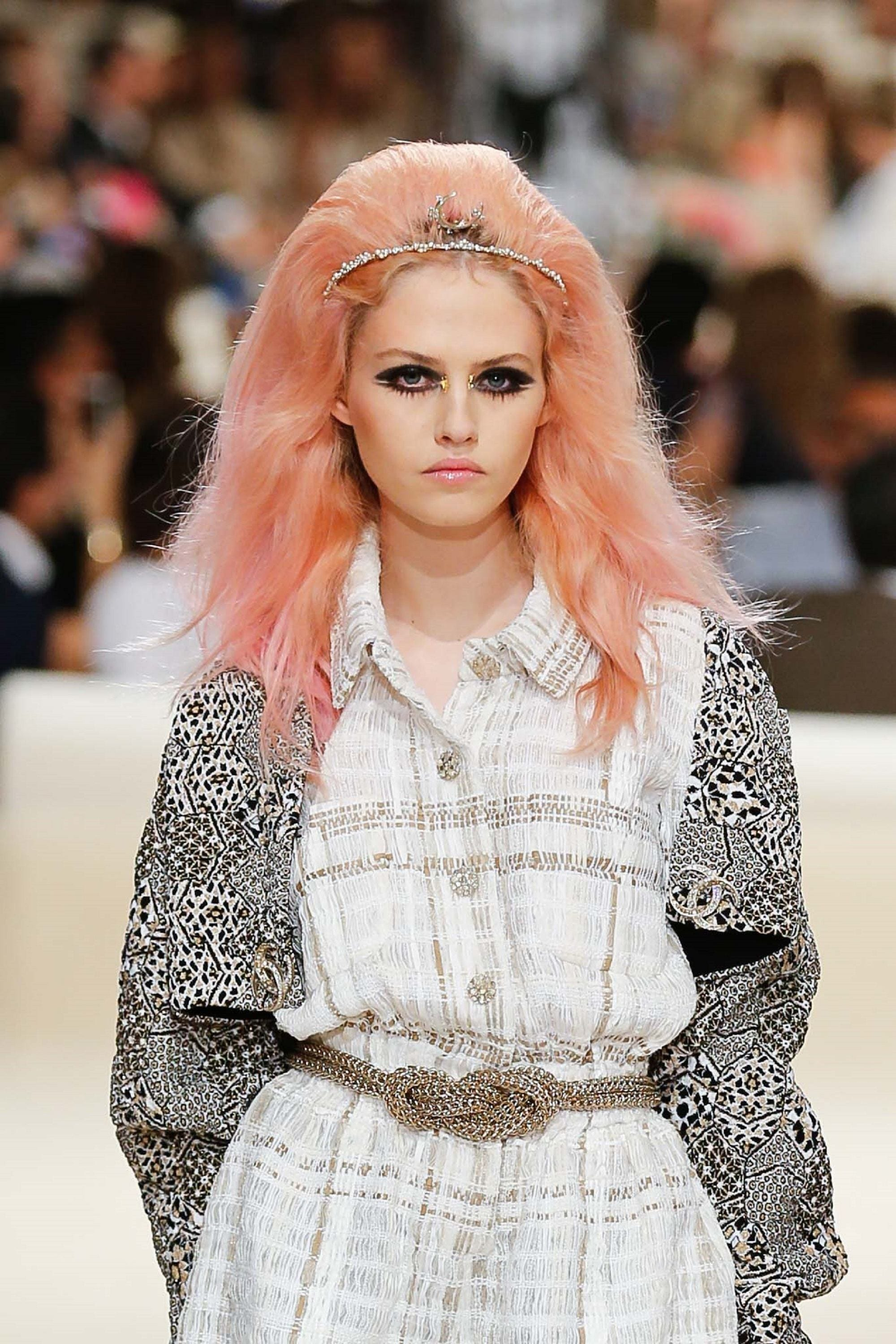 Hair color for fair skin: Caucasian model with long voluminous peach hair wearing a white and gray dress on the runway